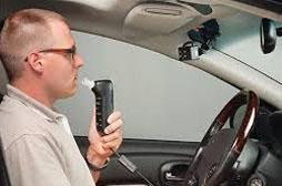 Man Sitting in Car Using Alcohol Breath Monitor