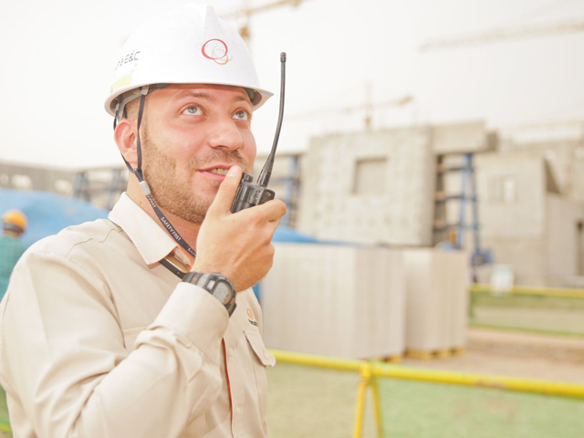 Man in hard hat using handheld radio at industrial site